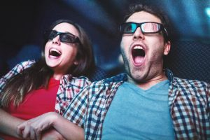 Closeup of mid 20's couple screaming while wathcing a movie at movie theater. Both wearing 3-d glasses and keeping their mouth open. She grabbed his hand. Low angle shot, toned image.